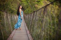 Belle fille sur le pont en bois suspendu Image stock