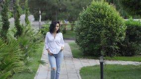 Belle fille tatar dans les promenades de parc sur le trottoir banque de vidéos