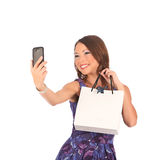 Belle fille tenant des paniers et prenant le selfie avec le téléphone portable d'isolement sur le blanc images libres de droits