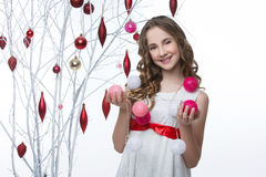 Belle fille tenant l'arbre proche avec des décorations de Noël image stock