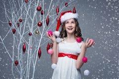Belle fille tenant l'arbre proche avec des décorations de Noël photographie stock libre de droits
