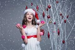 Belle fille tenant l'arbre proche avec des décorations de Noël images libres de droits