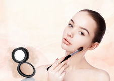 Belle fille tenant la brosse de maquillage pour la base image libre de droits