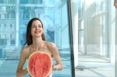 Belle fille tenant la moitié de la pastèque images libres de droits