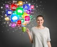 Belle fille tenant la tasse de café avec les icônes colorées de media Photos libres de droits