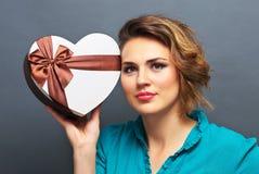 Belle fille tenant le cadeau sous forme de coeur Images libres de droits