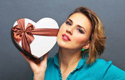 Belle fille tenant le cadeau sous forme de coeur Photographie stock libre de droits