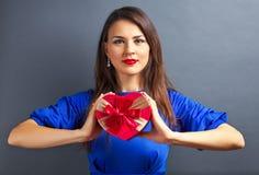 Belle fille tenant le cadeau sous la forme de coeur Photos stock