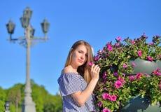 Belle fille tenant le lit de fleur proche devant un s antique Photographie stock libre de droits