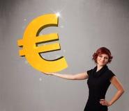 Belle fille tenant un grand signe d'euro de l'or 3d Photos stock