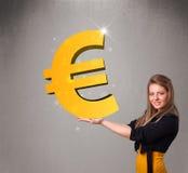 Belle fille tenant un grand signe d'euro de l'or 3d Images stock