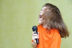 Belle fille tenant un microphone chantant et dansant Image libre de droits