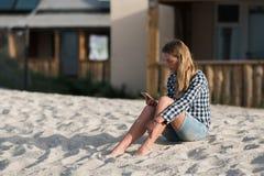 Belle fille tenant un smartphone dans les mains sur la plage près du sable de bord de mer à l'arrière-plan Images stock