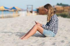 Belle fille tenant un smartphone dans les mains sur la plage près du sable de bord de mer à l'arrière-plan Photos libres de droits