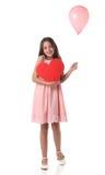 Belle fille tenant une forme rouge de coeur et un ballon rose Photos libres de droits