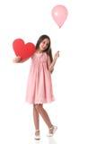 Belle fille tenant une forme rouge de coeur et un ballon rose Photos stock