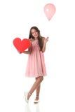 Belle fille tenant une forme rouge de coeur et un ballon rose Photographie stock libre de droits