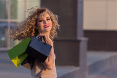 Belle fille tournant autour avec des paniers et souriant dans l'appareil-photo Jeune femme marchant après vente de mail photo stock