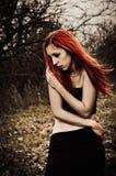 Belle fille triste rousse parmi les arbres d'automne Photo stock