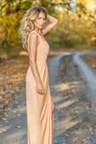 Belle fin blonde de femme vers le haut de portrait Yeux bleus, cheveux courbés Milieux d'automne Images stock