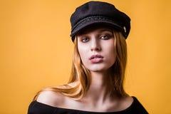 Belle fin de visage de cheveux blonds de femme vers le haut de studio de portrait sur le jaune Fille dans le chapeau noir regarda image libre de droits