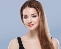 Belle fin de visage de femme vers le haut de jeune studio de portrait sur le bleu Images stock