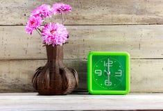 Belle fleur rose en bois de pot, horloge verte sur le backgro en bois Images libres de droits