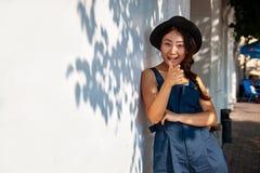 Belle foglie dell'albero di acero che emettono luce al sole Giovane donna asiatica in casuale contro la parete bianca con le ombr fotografia stock