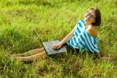 Belle free lance della donna che lavorano con il computer portatile all'aperto Donna s Fotografie Stock Libere da Diritti