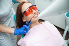 Belle, gaie fille dans la chaise du dentiste Demande de règlement dentaire Clinique dentaire image stock
