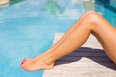 Belle gambe abbronzate delle donne dalla piscina fotografia stock