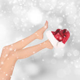 Belle gambe della donna, fondo di Natale Immagine Stock
