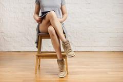 Belle gambe di una donna che legge un giornale Fotografie Stock Libere da Diritti