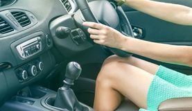 Belle gambe esili abbronzate dell'autista della donna in un'automobile Ragazza in vestito che conduce un'automobile immagini stock