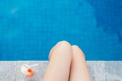 Belle gambe esili delle donne dalla piscina e dai cocktail tricolori freschi Vacanze estive, viaggio, concetto di vacanza Fotografia Stock Libera da Diritti