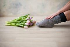Belle gambe femminili in calzini con un mazzo dei tulipani Immagine Stock Libera da Diritti