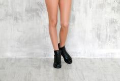 Belle gambe femminili esili in collant beige leggero e stivali neri di autunno su fondo grigio Fotografia Stock Libera da Diritti