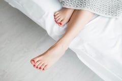 Belle gambe femminili sulla vista superiore del letto Fotografie Stock
