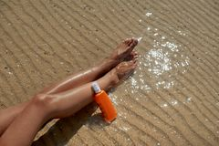 Belle, gambe governate del ` s della donna con una crema per proteggere solarizzazione dal sole di estate sul mare del fondo cure fotografie stock