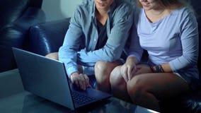 Belle giovani coppie asiatiche che si siedono sul sofà con il computer della compressa nella stanza nella sera stock footage