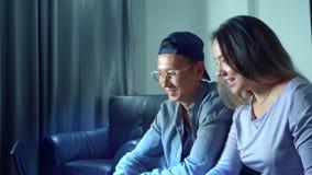 Belle giovani coppie asiatiche che si siedono sul sofà con il computer della compressa nella stanza nella sera video d archivio