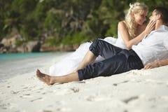 Belle giovani coppie che baciano sul tramonto che si trova sulla sabbia, tramonto t Fotografie Stock