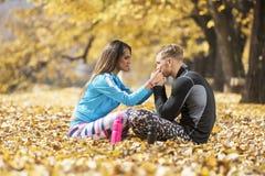 Belle giovani coppie che riposano e che baciano dopo il riuscito addestramento nel parco Fotografia Stock