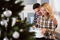 Belle giovani coppie che si siedono dalla finestra con le decorazioni del ` s del nuovo anno e l'albero di Natale fotografie stock libere da diritti