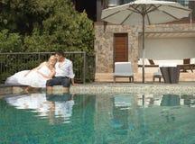 Belle giovani coppie che si trovano vicino allo stagno prima delle nozze sotto Fotografie Stock