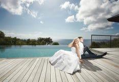 Belle giovani coppie che si trovano vicino allo stagno prima delle nozze sotto Immagini Stock