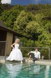 Belle giovani coppie che si trovano vicino allo stagno prima delle nozze sotto Immagine Stock
