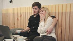 Belle giovani coppie con il computer portatile in caffè, stanno guardando insieme il film ed il caffè bevente fotografie stock