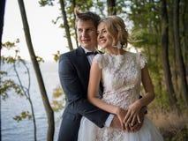 Belle, giovani coppie di nozze sui precedenti di bella n fotografia stock