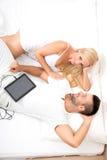 Belle giovani coppie facendo uso di un PC della compressa a letto fotografia stock
